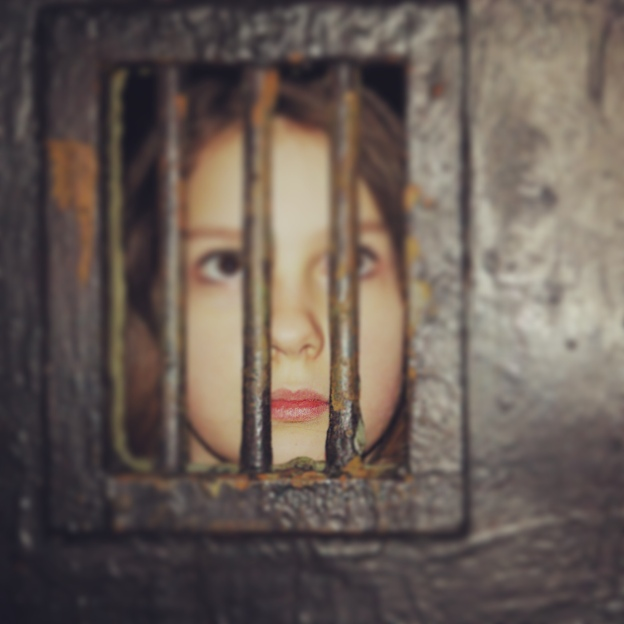 Jenna poses behind bars in a memorial to Auschwitz