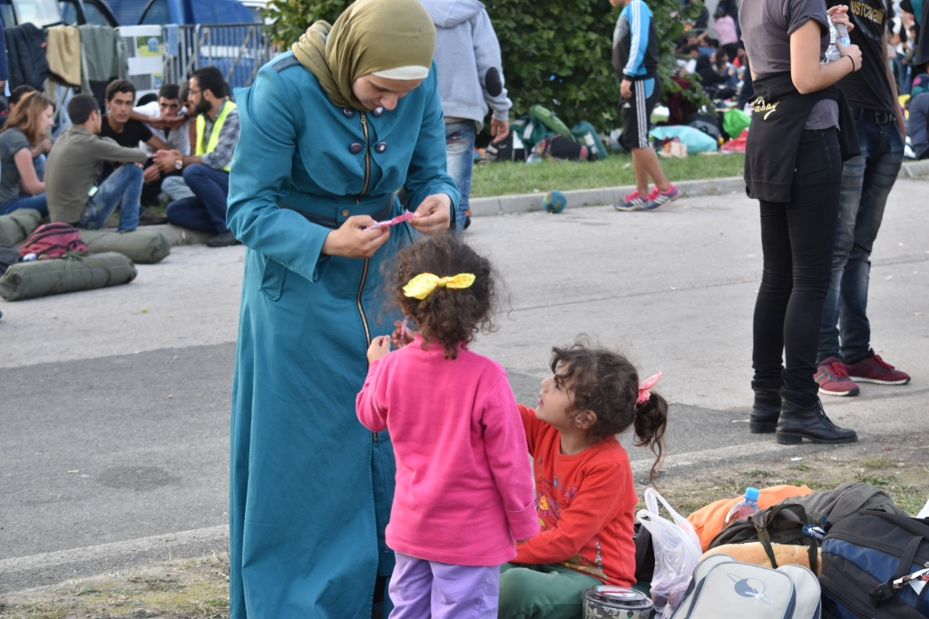 a Syrian mother helps her two sweet girls open a lollipop